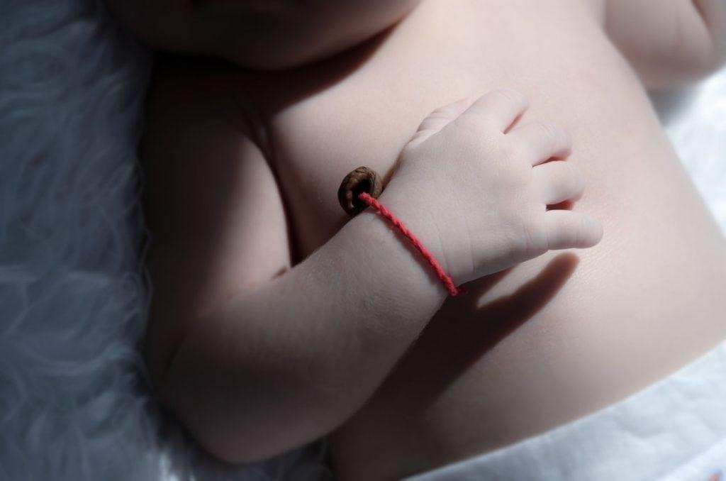 Czerwona nitka u dziecka na ręce