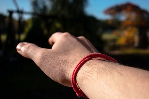 Czerwona bransoletka na ręce